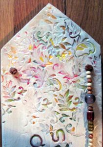 """Few Words"" is a clay image, 15X4X .5 inches, embellished with acrylic painting, beads and weaving.... $75.00"