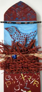 """More Words"" is rusty brown and sky blue with a bird image, words spilling down the center to delicate, emerging foliage. It has a ""nest-like"" raffia weaving"