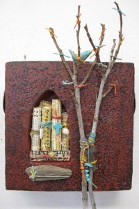 "THE ALTAR SERIES: SACRED MESSAGES is a clay box-like ""altar"" with a cathedral window shape cut in it, and filled with scrolls, a bundle of dried twigs are attached along with a clay bird perched on top."