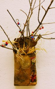 Vertical clay packet with postage stamps, dried stems, beads, wire and metal bird shape