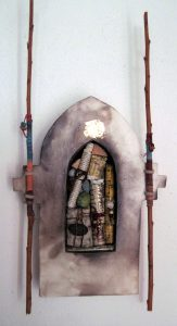 """Cathedral window shaped clay with a niche filled with embellished rolled paper """"scrolls"""" and stones. Wrapped clay twigs are attached to the sides and extend upward approximately 15 inches."""